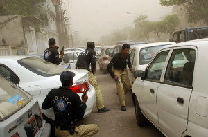 Policemen advancing towards gunmen attacking an Ahmadi mosque in Lahore's Garhi Shahu neighborhood take cover after an explosion