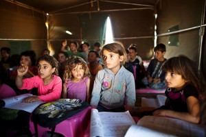 In this Tuesday, Aug. 11, 2015 file photo, Syrian refugee children attend a class at a makeshift school set up in a tent at an informal tented settlement near the Syrian border on the outskirts of Mafraq, Jordan.  Forty percent of children from five conflict-scarred Middle Eastern countries are not in school, the U.N. child welfare agency said in a report Thursday, Sept. 3, 2015, warning of a lost generation and a dim future for the region. UNICEF said 13.7 million out of 34 million school age children in Syria, Iraq, Yemen, Libya and Sudan are not getting an education, almost double the number five years ago. (AP Photo/Muhammed Muheisen, File)