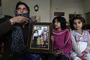 Rafiatta (L), from the Ahmadi community, gestures while showing her family photograph at her house in the town of Rabwa December 9, 2013. Rafiatta, who asked her last name not be used, moved to Rabwa after gunmen killed her husband in 2010 in front of their young children. Three years ago, 86 Ahmadis were killed in two simultaneous attacks on Friday prayers in Lahore. There have been no mass attacks since then, but targeted killings are rising: last year 20 Ahmadis were killed, up from 11 in 2009. Picture taken on December 9, 2013. REUTERS/Zohra Bensemra (PAKISTAN - Tags: CRIME LAW CIVIL UNREST RELIGION)