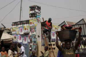 Men walk in front election posters at an open market in Kano March 27, 2015. Nigerian President Goodluck Jonathan warned against violence ahead of Saturday's presidential election as people began stockpiling food, cash and fuel for fear of clashes. Jonathan will face former military ruler Muhammadu Buhari in what is seen as the closest presidential race since the end of military rule in 1999. REUTERS/Goran Tomasevic   - RTR4V4QA